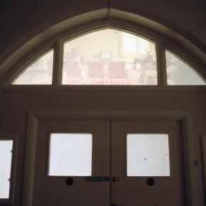 Back projection of empty hospital wards on window above ward doors.